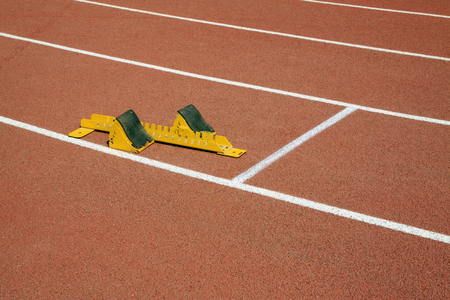 yellow block: yellow starting block and athletes, closeup of photo