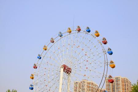 millennium wheel: ferris wheel and building in a park, closeup of photo