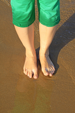 crus: ladys foot on the sea beach, closeup of photo