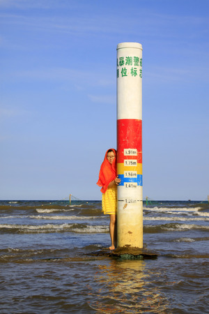 the surge: JINGTANG PORT - AUGUST 29: a girl visiting nearby storm surge alert water level mark, on August 29, 2015, Jingtang Port, hebei province, China.