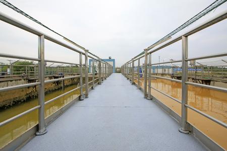 sedimentation: sewage treatment plant aerobic reaction pool channel and handrail, closeup of photo Stock Photo