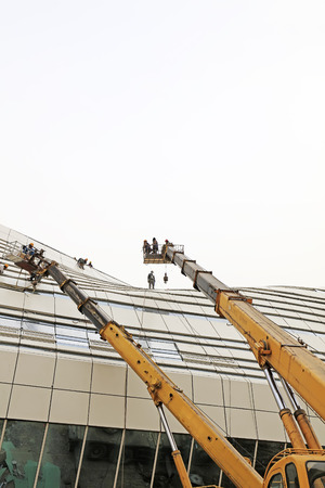 rigidity: crane arm and glass curtain wall in a construction site
