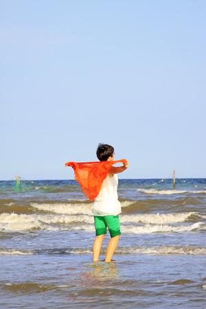 Una signora in piedi vicino alla spiaggia del mare