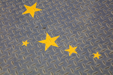 trample: Yellow stars in the checkered plate, closeup of photo