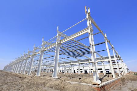 unfinished building: steel girder truss under blue sky, closeup of photo