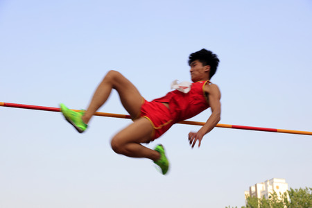 high jump: men high jump athletes in the playground Editorial