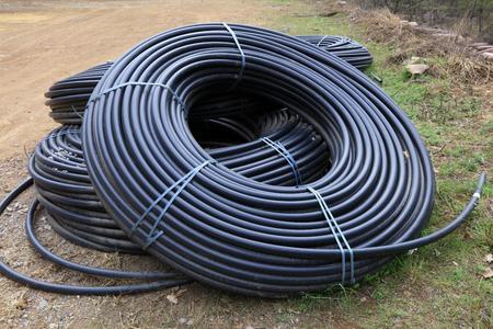 kunststoff rohr: Black plastic pipe curled up together