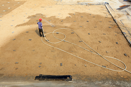 property development: workers watering in the construction site Editorial