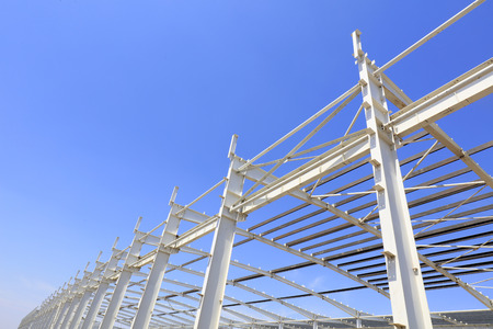 steel girder truss under blue sky, closeup of photo