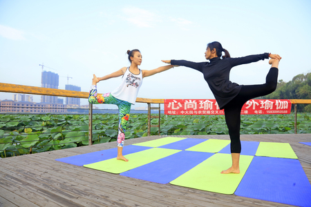 Tangshan City - September 3: women doing yoga exercise in the park, on September 3, 2016, tangshan city, hebei province, China. Editorial