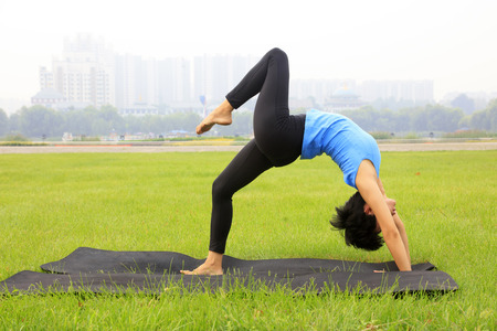 woman doing yoga exercise in the park, China Editorial