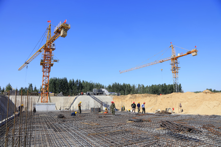 Luannan County - September 28: construction workers and tower crane in the construction site, on September 28, 2016, Luannan County, Hebei province, China