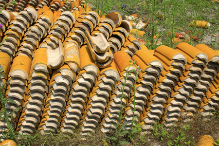 Yellow glazed tiles stacked in the grass