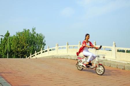 girl ride electrombile through the bridge