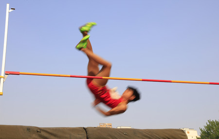 cross legs: men high jump athletes in the playground Stock Photo