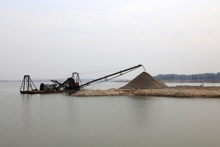 Simple sand dredger by river bank Stock Photo