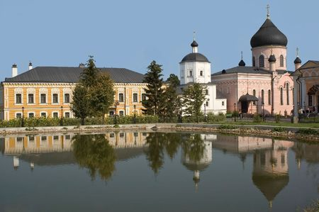 monastery is reflected in lake with water photo