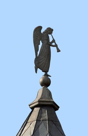angel on a roof of a monastery against the blue sky photo