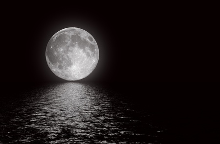 The full moon in the night sky reflected in water photo