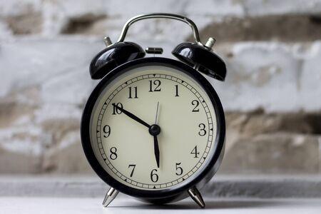 Retro alarm clock on table on brick wall background Zdjęcie Seryjne