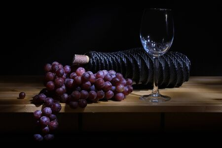 Bottle of red wine (bio wine) with an empty wine glass with grapes, herbs and nuts on a wooden background background of an old wooden table