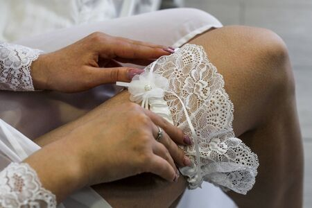 Hands of the bride straightens white lace wedding garter