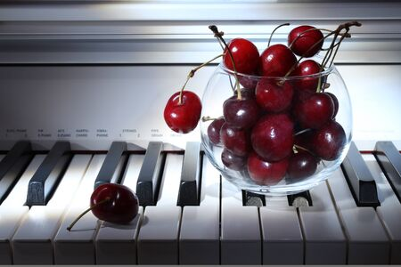 Cherries vase on piano keys closeup. Music concept. Picture of wallpaper. Design concept.