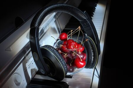 Beautiful ripe juicy red cherry berries lie with headphones on the white keys of the classical piano musical instrument, unusual design, beautiful background with berries on a musical theme. musical c