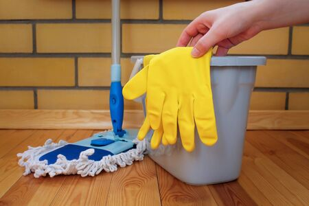 Cleaning equipment. Mop, plastic bucket and rubber gloves, Hand reaches for the glove, Cleaning concept