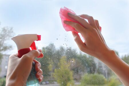 Female hand cleaning a window with a rag and spray detergent. Housekeeping concept, housekeeping concept