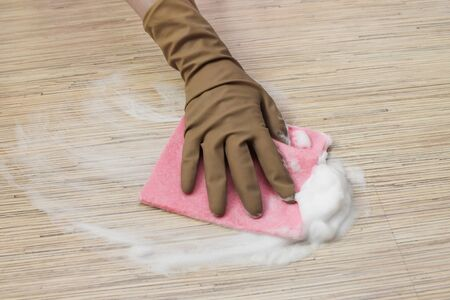 A hand washes the floor with a gloved hand with a rag and foam from a cleaning product. Cleaning, home cleaning concept