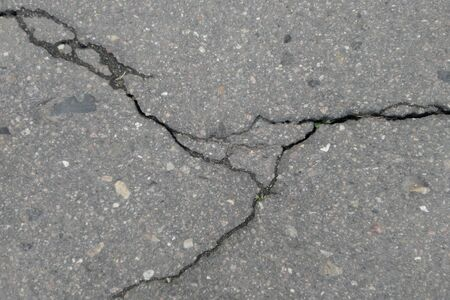 Extreme cold and heavy rains washed away asphalt road and formed numerous cracks and dangerous failures