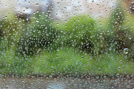 Raindrops on the window. Drops of water or rain drops on window glass with blur buildings background.