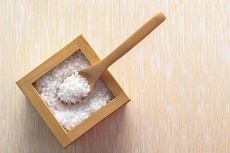 Salt in a wooden spoon top view. Salt as seasoning with place for text 版權商用圖片