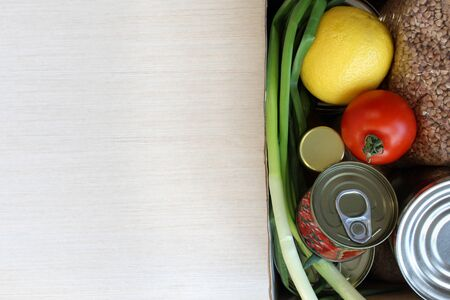 Food supplies crisis food stock for quarantine isolation period on light background. Canned food, buckwheat, lemon, tomato, green onion. Food delivery, Donation, coronavirus quarantine. Copyspace. Stok Fotoğraf
