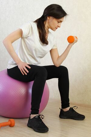 Beautiful woman exercising with dumbbells at home. home fitness workout. stop coronavirus COVID-19. Quarantine time Stock Photo