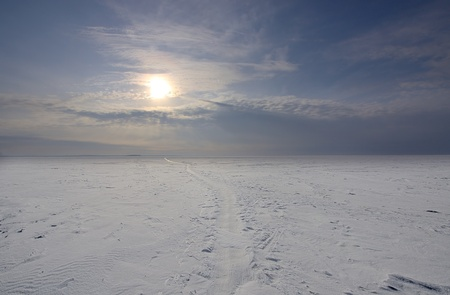 View of  snow covered  large space and  low sun on  blue sky, Russia. photo