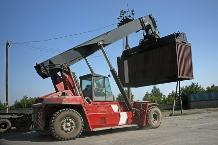 car hoist: Large forklift of containers in  loading area on  side.