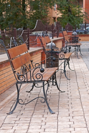 Wrought iron bench outside  house in  row, Russia. photo