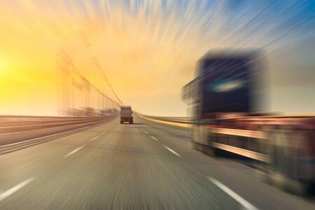 Wazige beweging van vrachtwagen en asfaltweg in de schemering