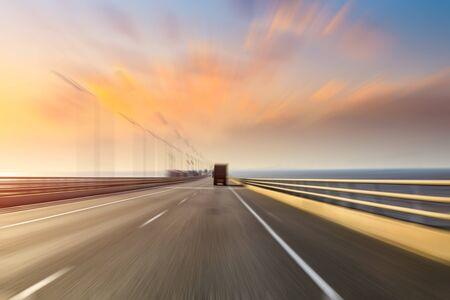 Wazige beweging van vrachtwagen en asfaltweg in de schemering Stockfoto