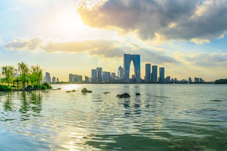 Beautiful city skyline and tranquil lake in Suzhou at sunset