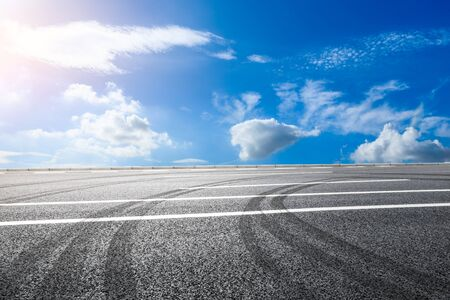 Empty asphalt road and blue sky with white clouds in summer