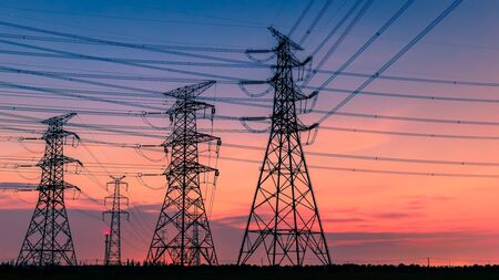 High voltage power tower and nature landscape at sunset
