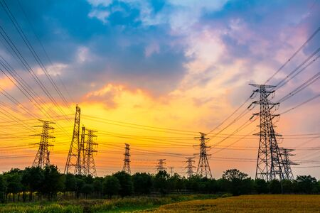 Industrial high voltage electricity tower and beautiful nature landscape at summer sunset Stockfoto