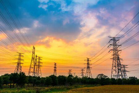 Przemysłowa wieża energetyczna wysokiego napięcia i piękny krajobraz przyrody o letnim zachodzie słońca Zdjęcie Seryjne