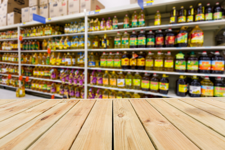 food shop: Wood table top and Supermarket fuzzy edible oil background