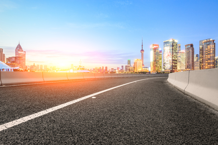 Asphalt road and modern cityscape at sunset in Shanghai Stock Photo