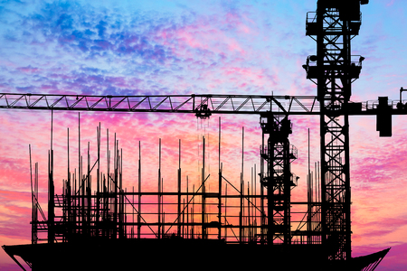 unfinished building: Crane and building construction site at sunset