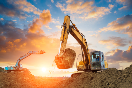 excavator in construction site on sunset sky background 스톡 콘텐츠